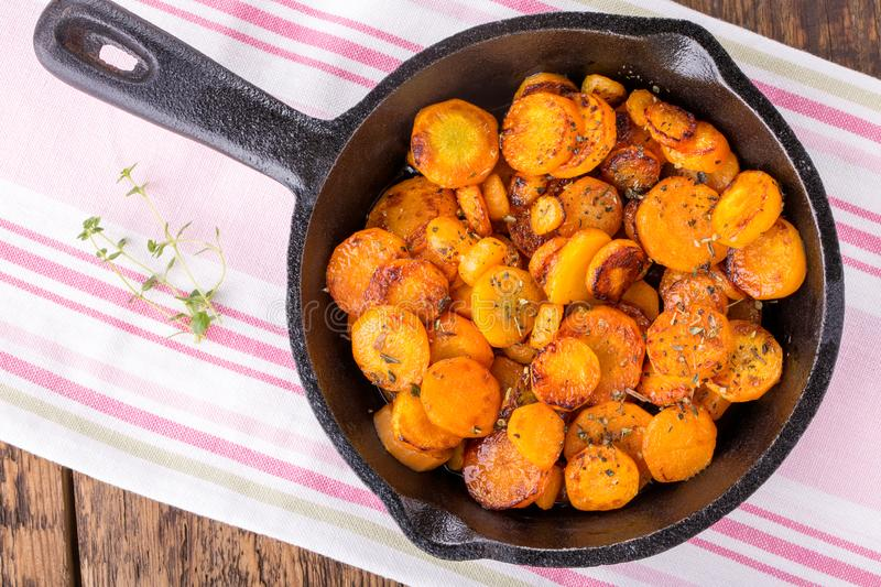Sliced carrots roasted with herbs in a cast iron skillet royalty free stock photos