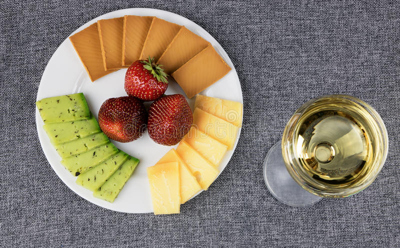 Sliced cheese on a plate with a glass of wine. royalty free stock photo