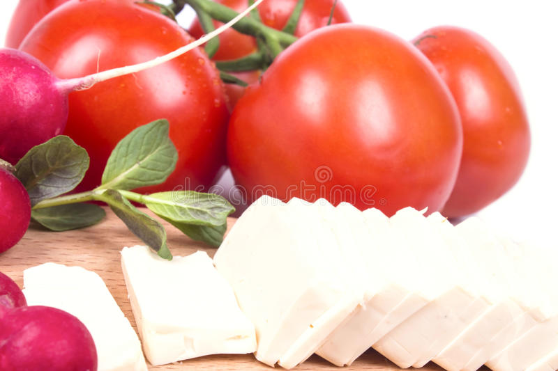 Sliced cheese on the table with fresh vegetables royalty free stock photography
