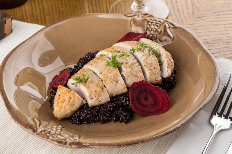 Sliced Chicken breast grilled and boiled black rice with beet on wooden table stock photo