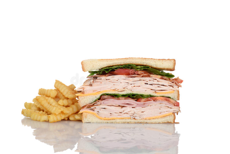 Sliced chicken club sandwich with french fries stock image