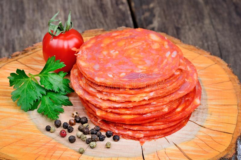 Sliced of chorizo salami with parsley and cherry tomato on a wooden cutting board royalty free stock photography