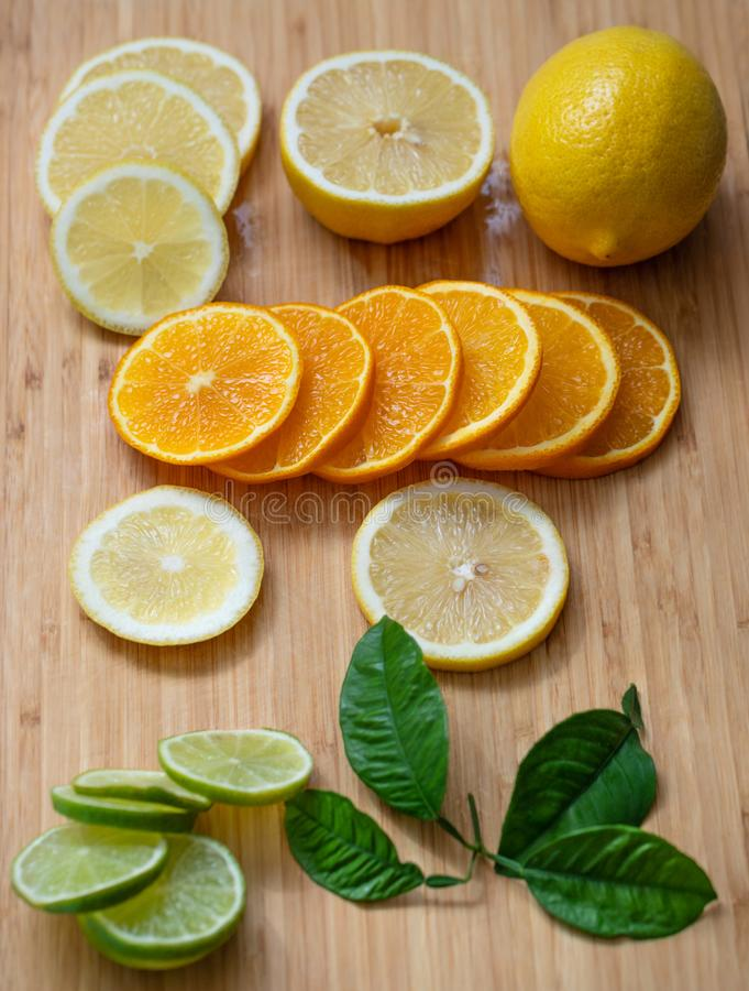 Sliced citrus fruit on a wooden chopping Board. Juicy ripe slices of orange, lemon and lime on wooden background. Fruit mix stock image