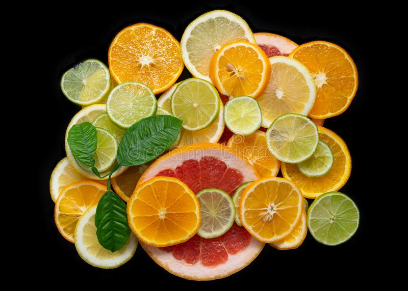 Sliced citrus fruits isolated on a black background close up, top view. Juicy ripe orange, tangerine, grapefruit, lime. Sliced citrus fruits isolated on a black royalty free stock image