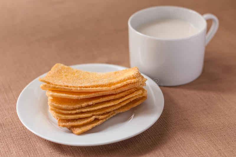 Sliced crispy bread in white ceramic dish. Sliced crispy bread in white ceramic dish with glass of milk on brown tablecloth background royalty free stock photography