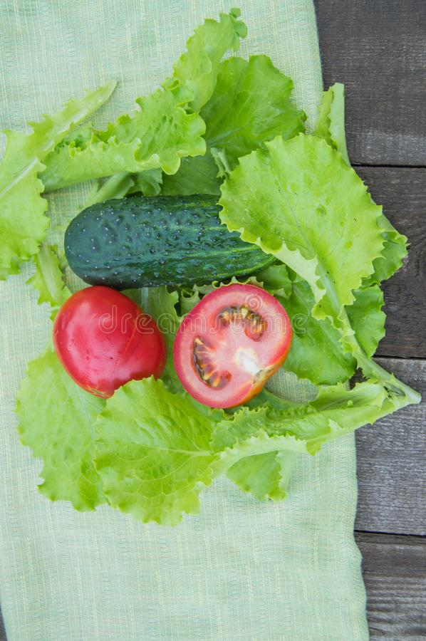 Sliced cucumbers and tomatoes lie on a green napkin, next to lettuce leaves, old dark wooden background, vertical shot.  stock images