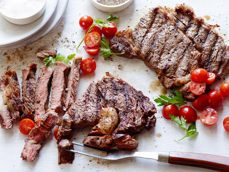 Sliced deep fried beef with tomatoes and herbs on the table royalty free stock photography