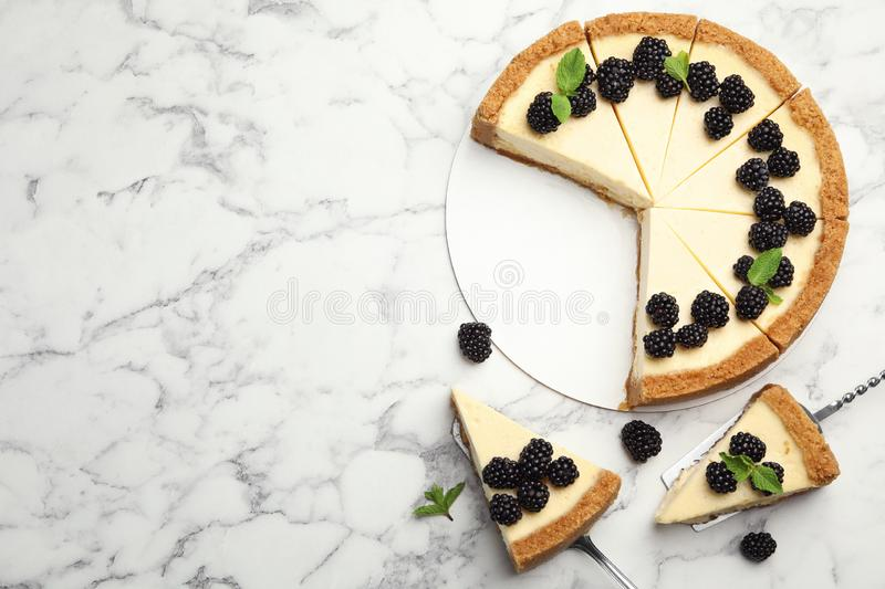 Sliced delicious cheesecake with blackberries on white marble background. Space for text. Sliced delicious cheesecake with blackberries on white marble royalty free stock photography