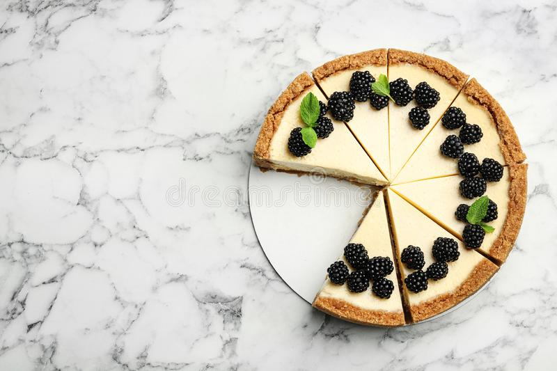 Sliced delicious cheesecake with blackberries on white marble background. Space for text. Sliced delicious cheesecake with blackberries on white marble royalty free stock images