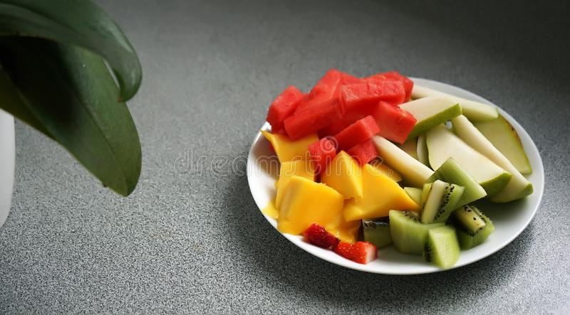 Sliced and diced exotic fruits served on a plate, with a plant in background stock photography
