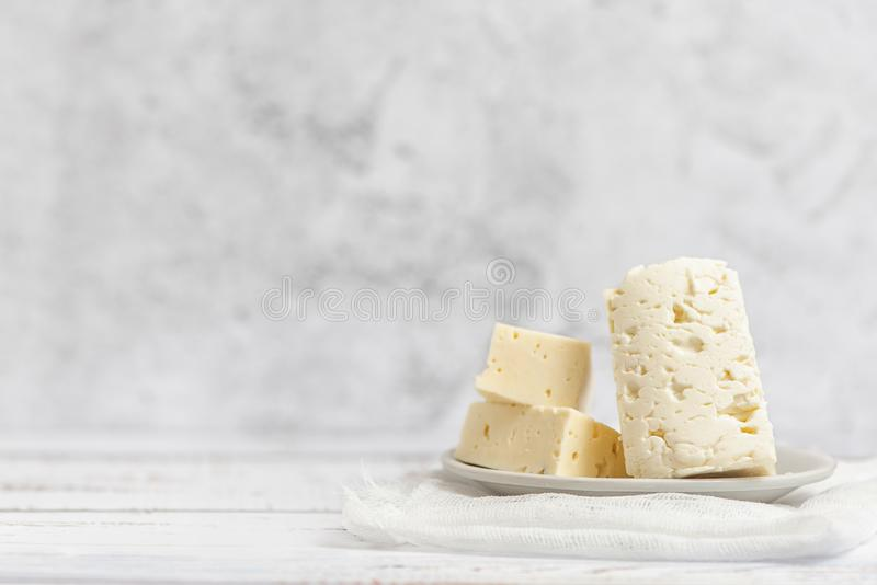 Sliced feta cheese on light background. High key. With copy space.  royalty free stock photo