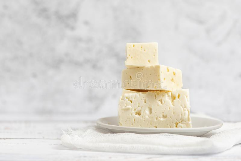 Sliced feta cheese on light background. High key. With copy space.  royalty free stock photography