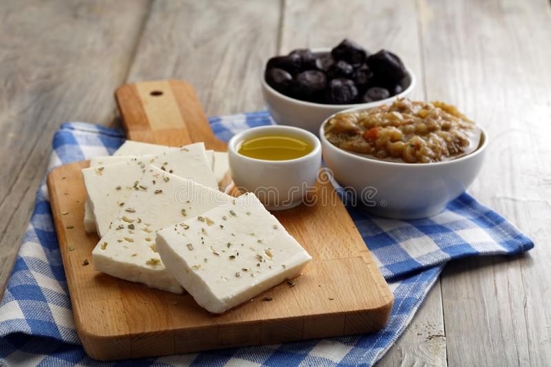Sliced feta cheese and olives stock photos