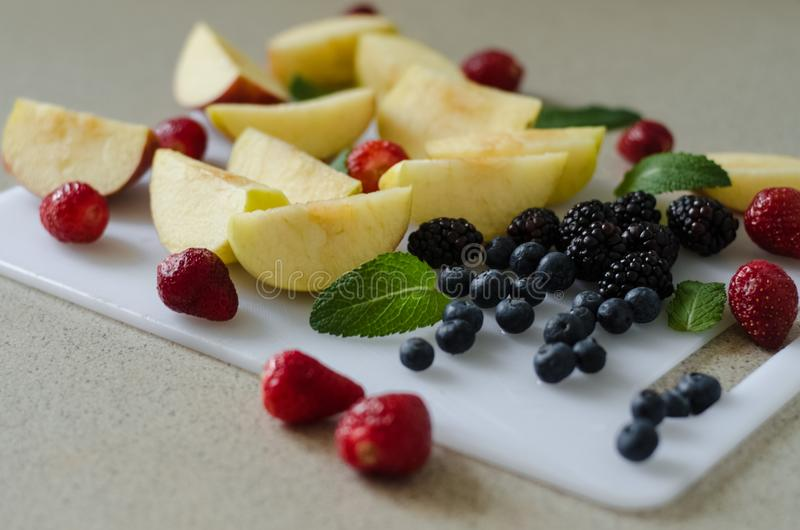 Sliced fresh apples, berries and mint leaves around, fresh summer fruits, ingredients for kompot stock photos