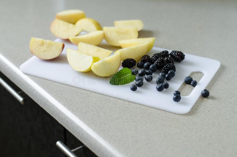 Sliced fresh apples, blueberries, blackberries and mint leaves around, fresh summer fruits from market stock image