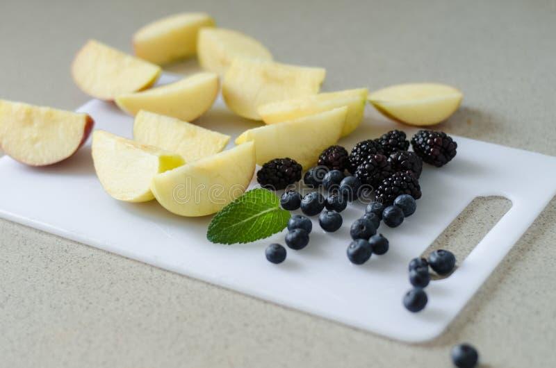 Sliced fresh apples, blueberries, blackberries and mint leaves around, fresh summer fruits stock photography