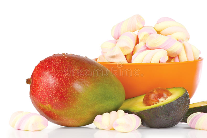 Sliced fresh avocado, mango and candies stock images
