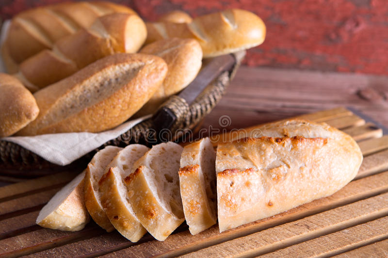 Sliced fresh baguette on a cutting board stock images