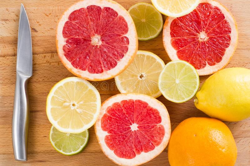 Sliced fresh citrus lemons, limes, grapefruits, oranges on a wooden cutting board with a metal knife, top view royalty free stock photos