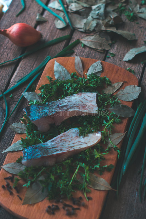 Sliced fresh fish with spices and parsley on a wooden board. Sliced fresh fish with spices and parsley on a wooden board royalty free stock photography