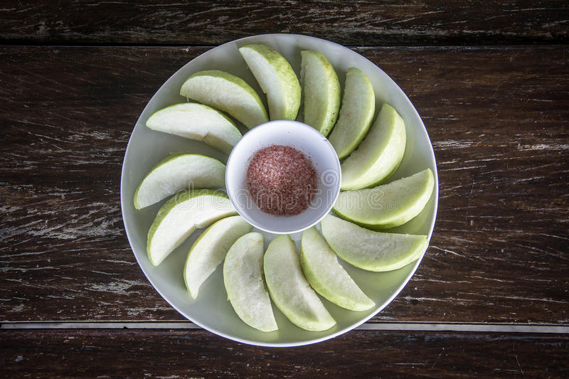 Sliced fresh guava serve with sweet sauce on wooden table stock image