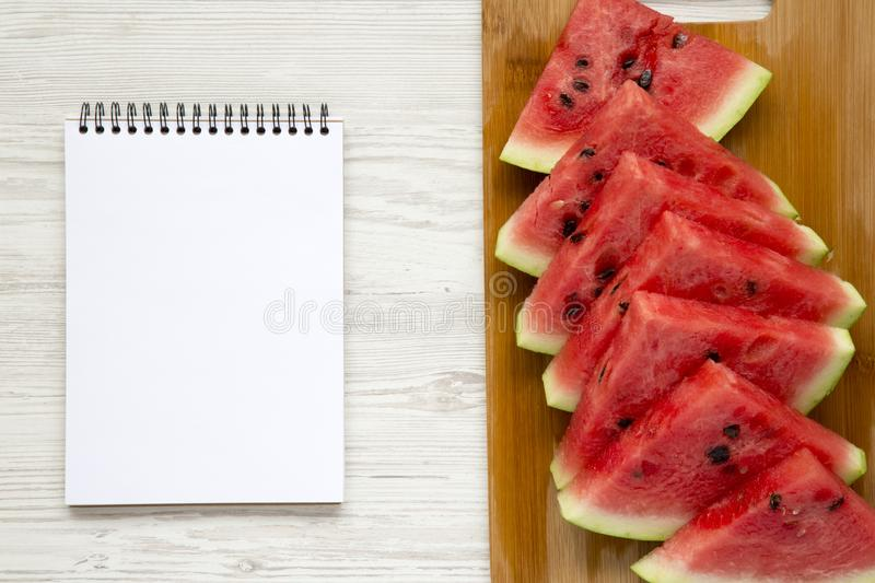 Sliced fresh ripe watermelon on cutting bamboo board with blank notebook over white wooden background, top view. stock photo