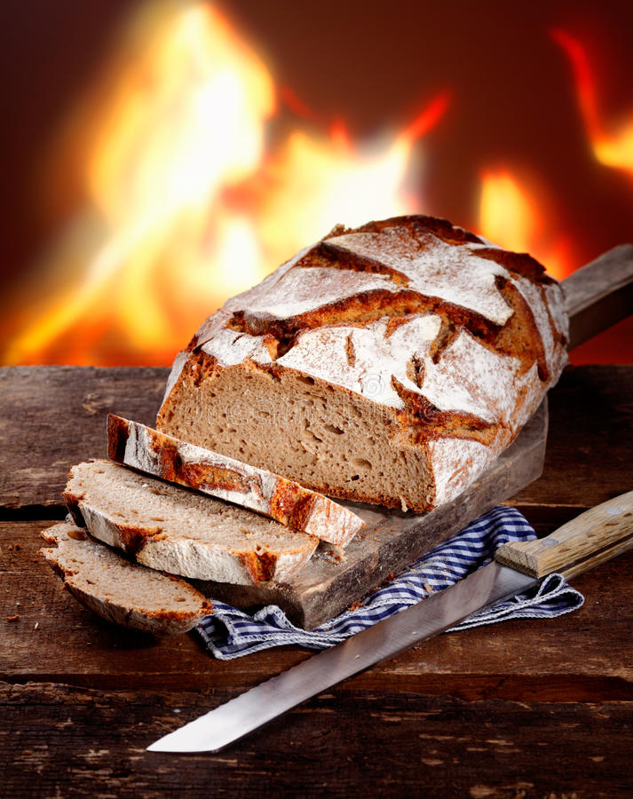Sliced fresh rye bread. On a rustic wooden table in front of a roaring fire royalty free stock photography