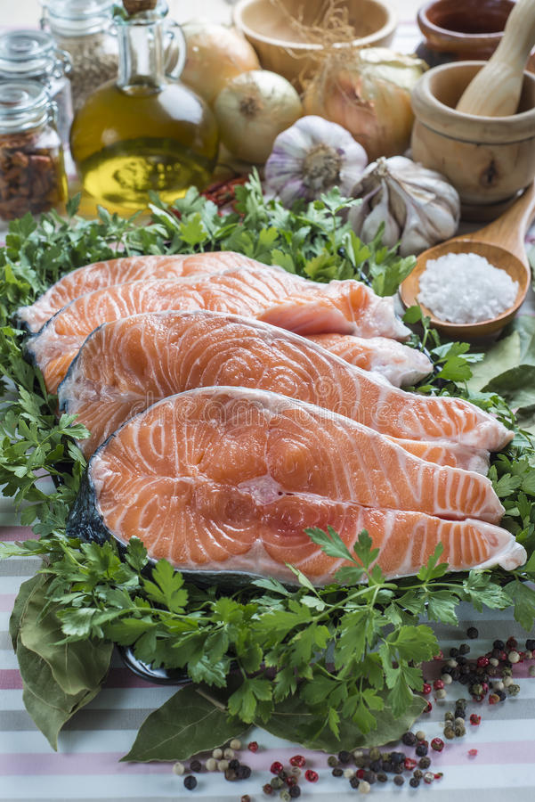 Sliced fresh salmon. A platter with sliced fresh salmon and ingredients to cook it on the table of the kitchen royalty free stock image