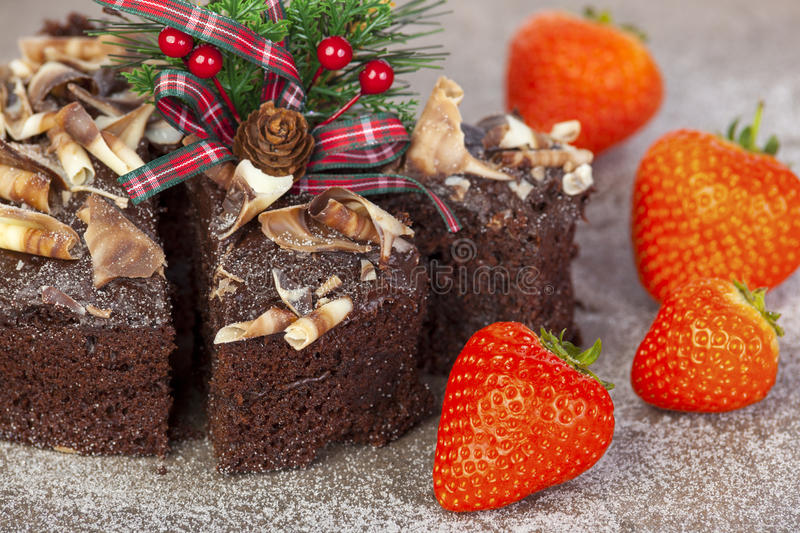 Sliced frosted chocolate christmas cake with fresh whole strawberrys stock photo