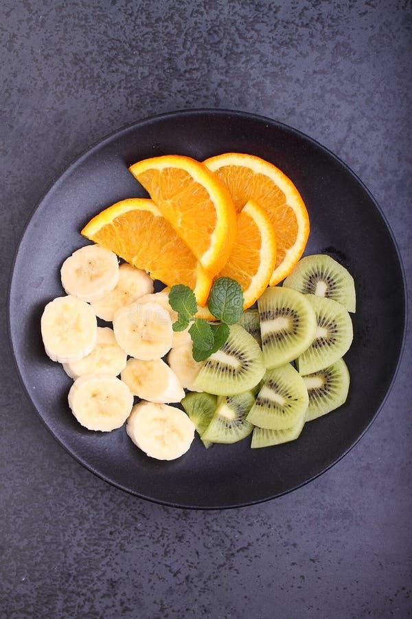 Sliced fruit (strawberries, kiwi, orange, banana). On a black plate stock photo