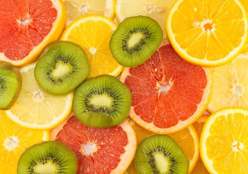 Sliced Fruits Background. Consisting of grapefruits, oranges, kiwi and lemons royalty free stock photo