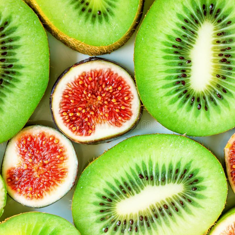 Sliced fruits background. Slices of juicy green kiwi and red figs.  stock photography