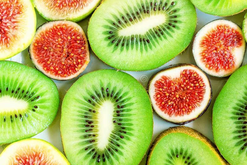 Sliced fruits background. Slices of juicy green kiwi and red figs. Sliced fruits background. Slices of juicy green kiwi and red figs royalty free stock photo