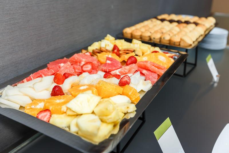 Sliced fruits and Sweet muffins on served table on a coffee break in the office. Sliced fruits and Sweet muffins on a served table on a coffee break in the stock images