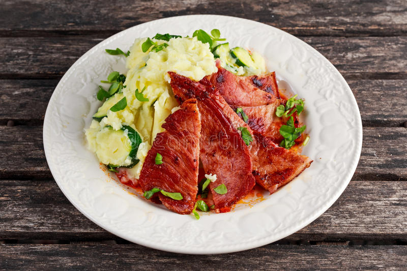 Sliced Gammon Steak with mashed potato on wooden background. stock images