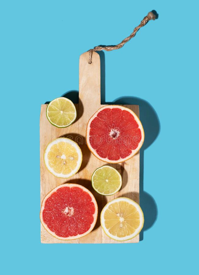Sliced grapefruit and lime on a wooden Board. Bright blue background royalty free stock photos