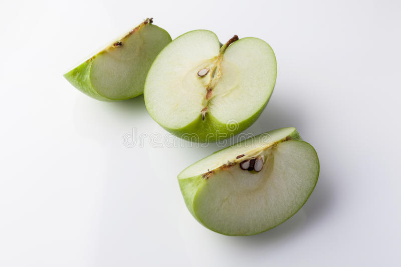 Sliced green apple from high angle on white. Sliced green apple half and two quarters on black background from high angle royalty free stock image