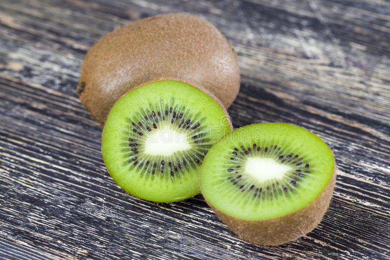 Sliced green kiwi. Fruit on a wooden table, cooking fruit dessert stock image