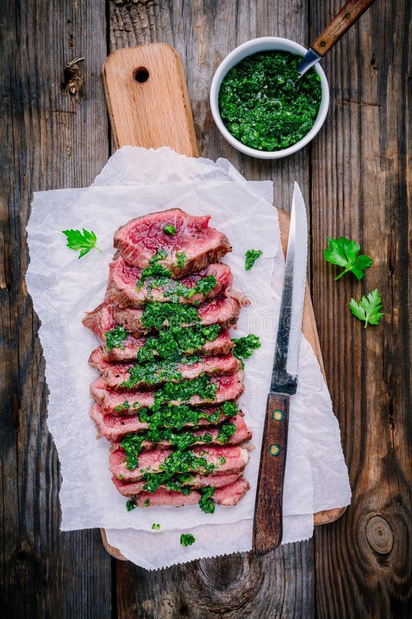 Sliced grillade grillfestnötköttbiff med grön chimichurrisås royaltyfria foton