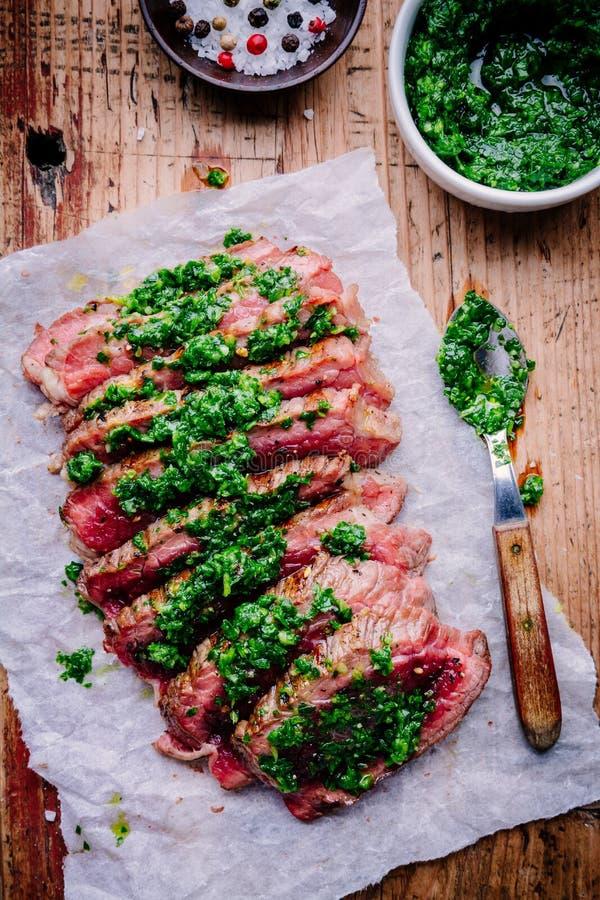 Sliced grillade grillfestnötköttbiff med grön chimichurrisås royaltyfria bilder
