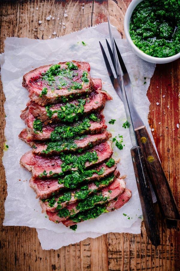 Sliced grillade grillfestnötköttbiff med grön chimichurrisås arkivbilder