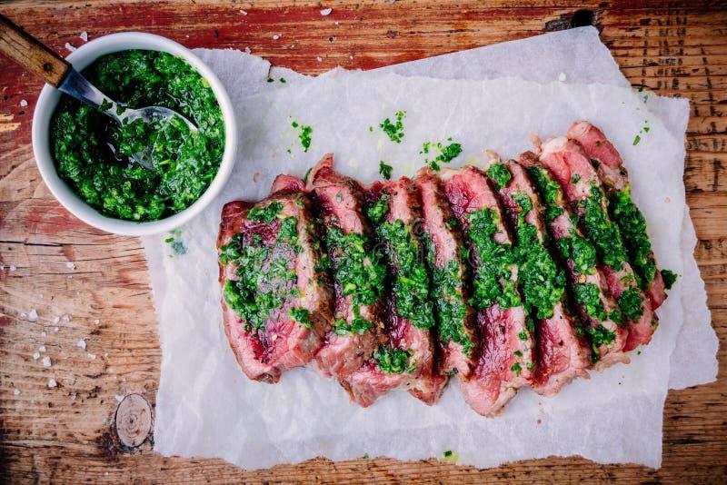 Sliced grillade grillfestnötköttbiff med grön chimichurrisås arkivfoton