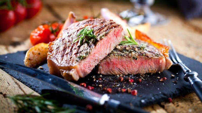 Sliced grillade köttgrillfestbiff Striploin med kniven, och gaffeln som snider uppsättningen på svart, stenar kritiserar royaltyfria bilder