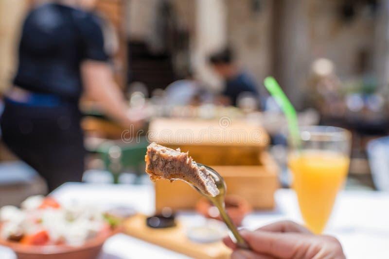 Sliced grillade lammkotletter på en gaffel Kvinnan har en matställe i en grekisk krog royaltyfri foto