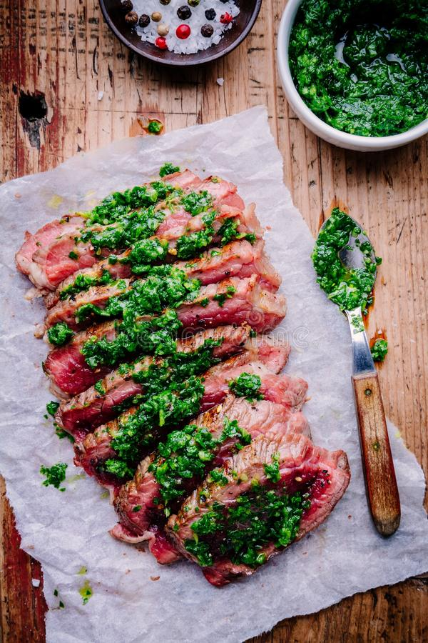 Sliced grilled barbecue beef steak with green chimichurri sauce royalty free stock images