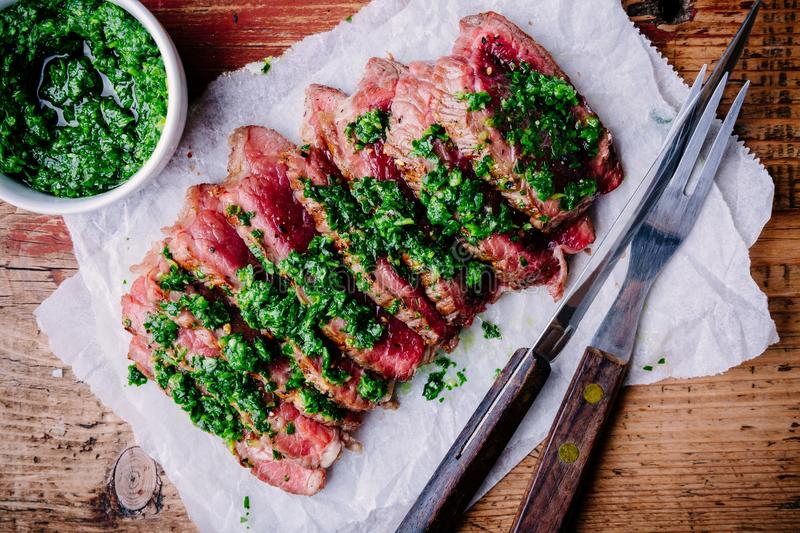 Sliced grilled barbecue beef steak with green chimichurri sauce royalty free stock photo
