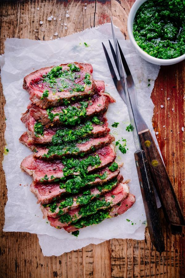 Sliced grilled barbecue beef steak with green chimichurri sauce stock images