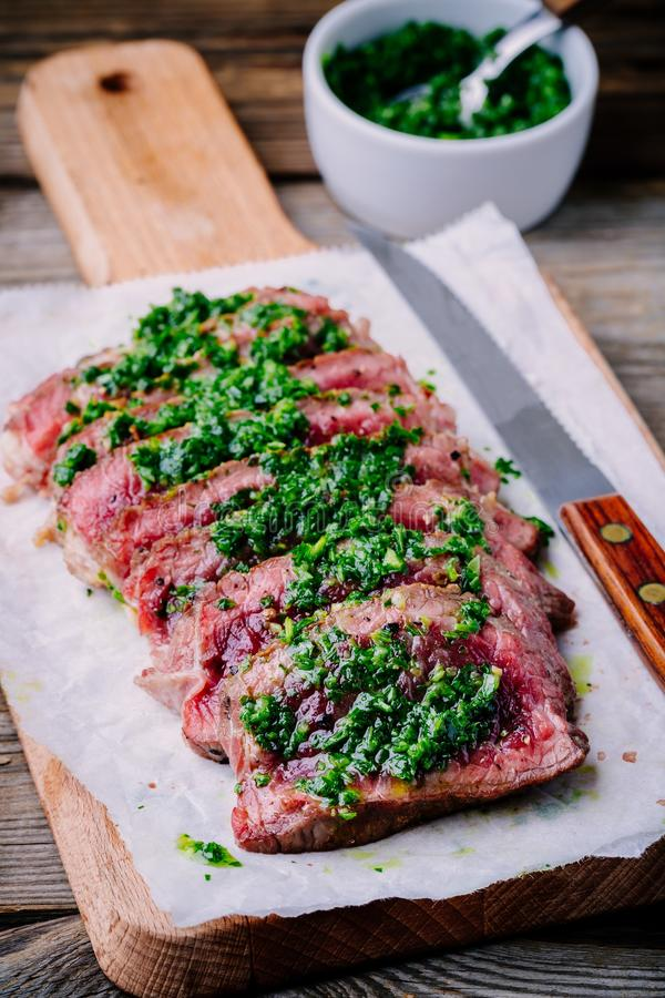 Sliced grilled barbecue beef steak with green chimichurri sauce stock photos