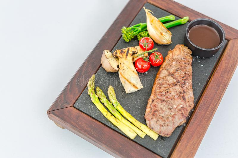 Gourmet grill menu. Beef steak grilled with vegetables on cutting board at dark background. Barbecue dish. Top view with copyspace royalty free stock images