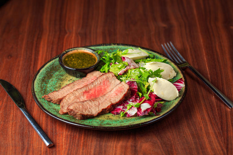 Sliced grilled beef steak with green leaves salad on rustic plate with cutlery. royalty free stock photos
